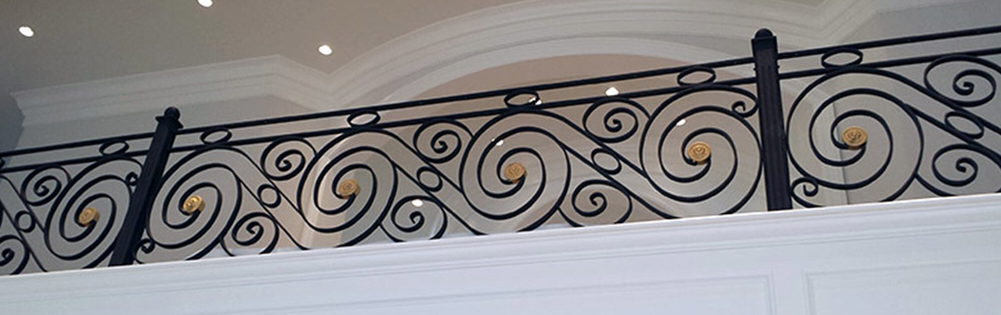 Custom wrought iron balcony railing featuring scroll balusters with gold accents